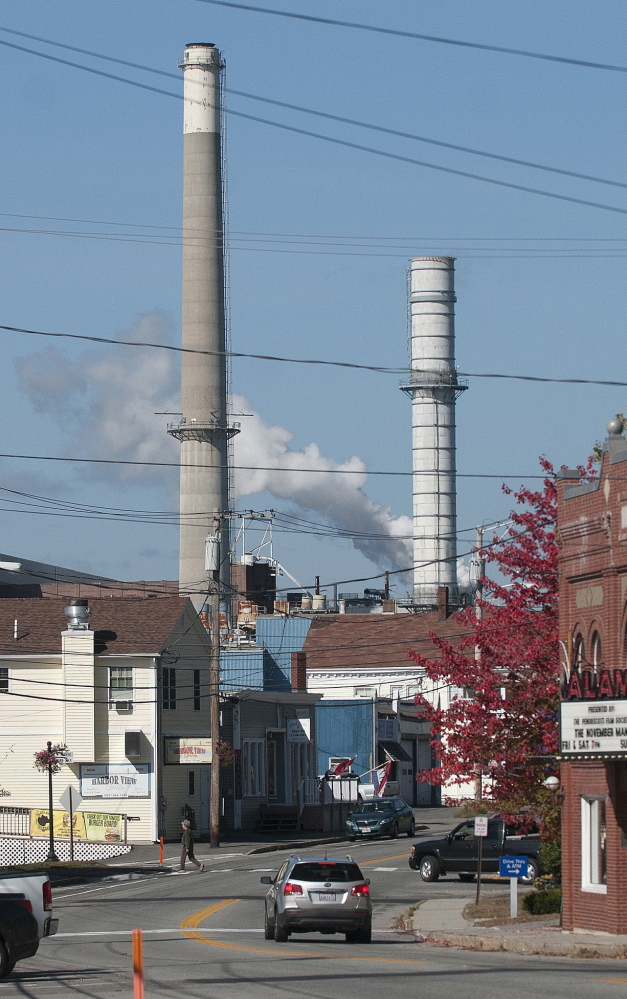 Smokestacks at Verso Paper's mill loom over the town of Bucksport last fall. More than 500 jobs were eliminated when the mill closed in December.