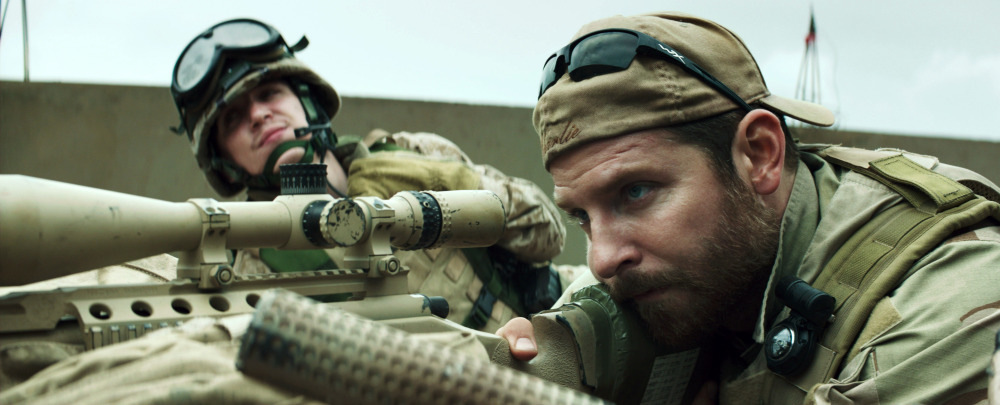 "Bradley Cooper, right, appears in a scene from ""American Sniper."" The movie has drawn criticism from some as military propaganda and then fierce defense from others who say veterans are underappreciated."