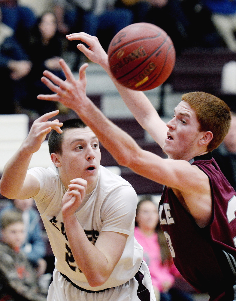 Kyle Kilfoil of Windham finds enough room to slip a pass past Nolan Smeeton of Noble. Windham improved its record to 9-4. Smeeton scored 30 points for Noble, which dropped to 2-11.