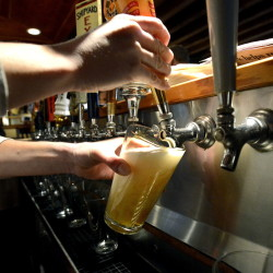 Bartender Melissa Cyr pours a pint at 3 Dollar Dewey's in Portland. A legislator is proposing a statewide law requiring that pints are poured at a full 16 ounces.