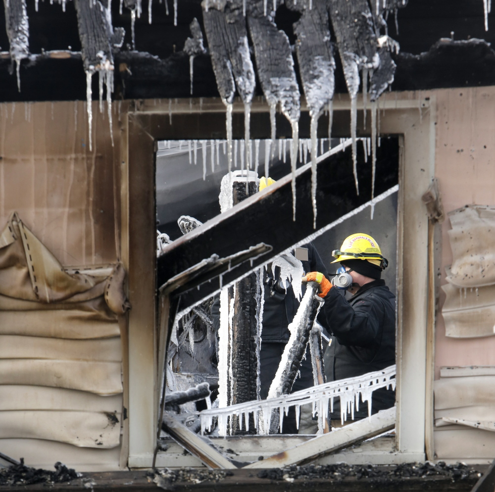 An investigator with the State Fire Marshal's Office looks over ice-covered debris inside the Americana Motel in Old Orchard Beach. The structure was due to be removed to make way for  a parking lot.
