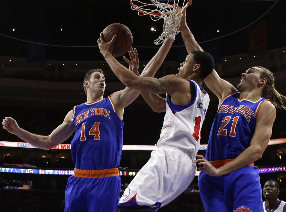 Philadelphia's K.J. McDaniels, center, goes up for a shot between Jason Smith, left, and Lou Amundson of the Knicks in Wednesday's game. The Knicks won their second straight, 98-91, after losing 16 straight.
