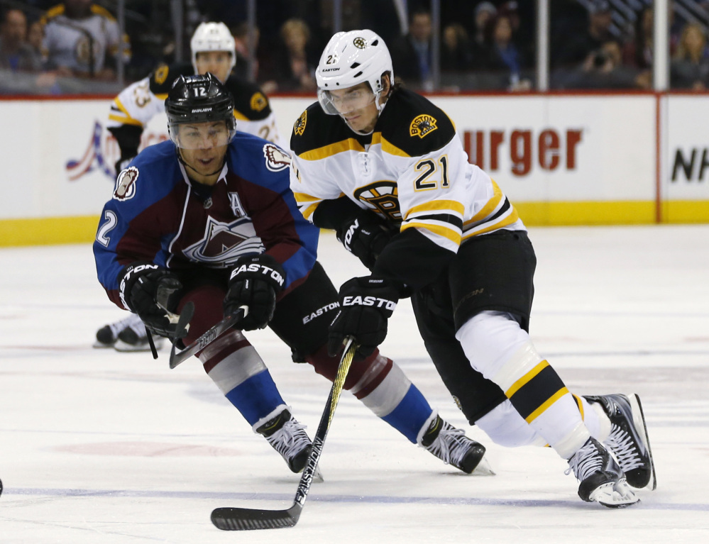 Boston Bruins right wing Loui Eriksson drives down the ice with the puck as Colorado Avalanche right wing Jarome Iginla defends in the second period of Wednesday night's game in Denver. The Avalanche won in a shootout.