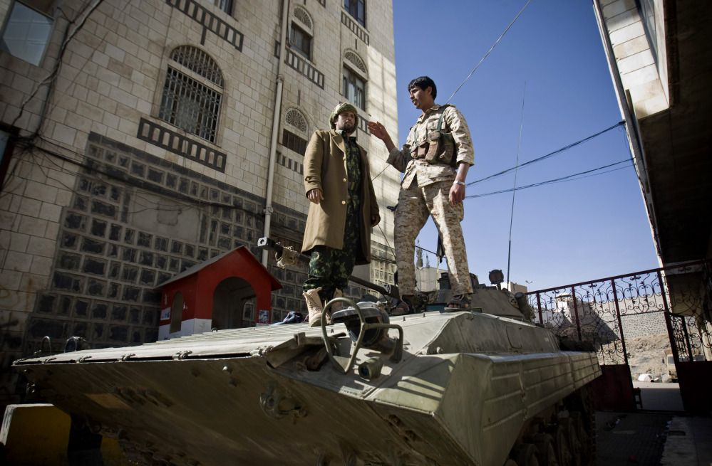 Houthi Shiite Yemeni wearing army uniforms stand atop an armored vehicle, which was seized from the army during recent clashes, outside the house of Yemen's President Abed Rabbo Mansour Hadi in Sanaa, Yemen, on Thursday.