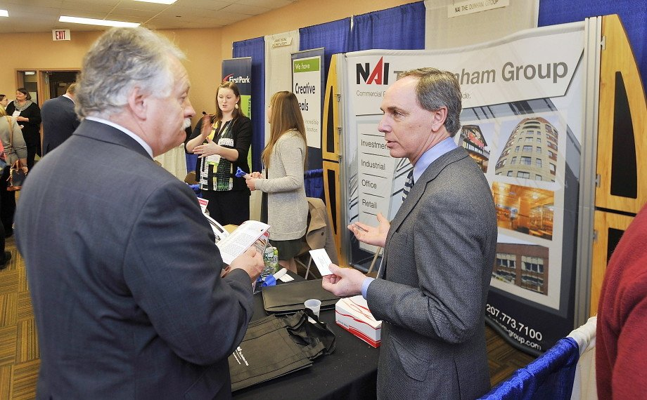 Charles Craig, with the  NAI Dunham Group, right, talks business with Jack Carr, senior vice president of Criterium Engineering, at the annual MEREDA forecasting conference Thursday at the Holiday Inn by the Bay in Portland. Gordon Chibroski/Staff Photographer