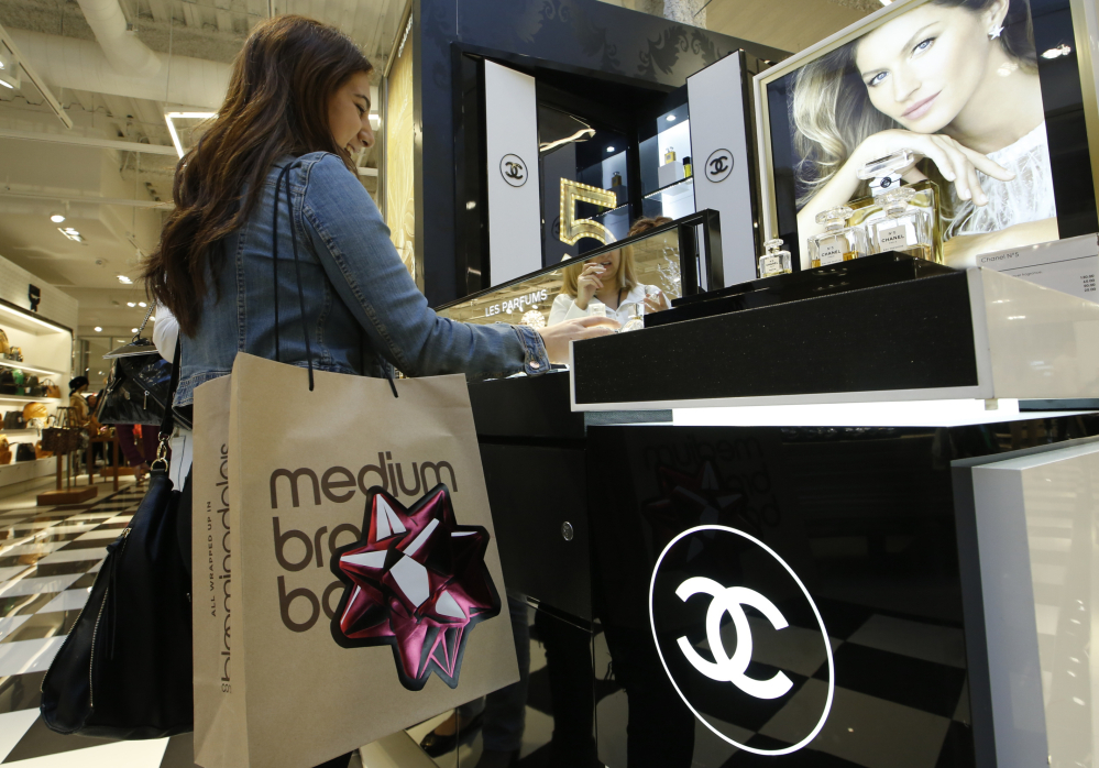 A shopper buys Chanel perfume at a Bloomingdale's in Glendale, Calif. Americans shouldn't expect a falling euro to result in bargains on high-end European goods.