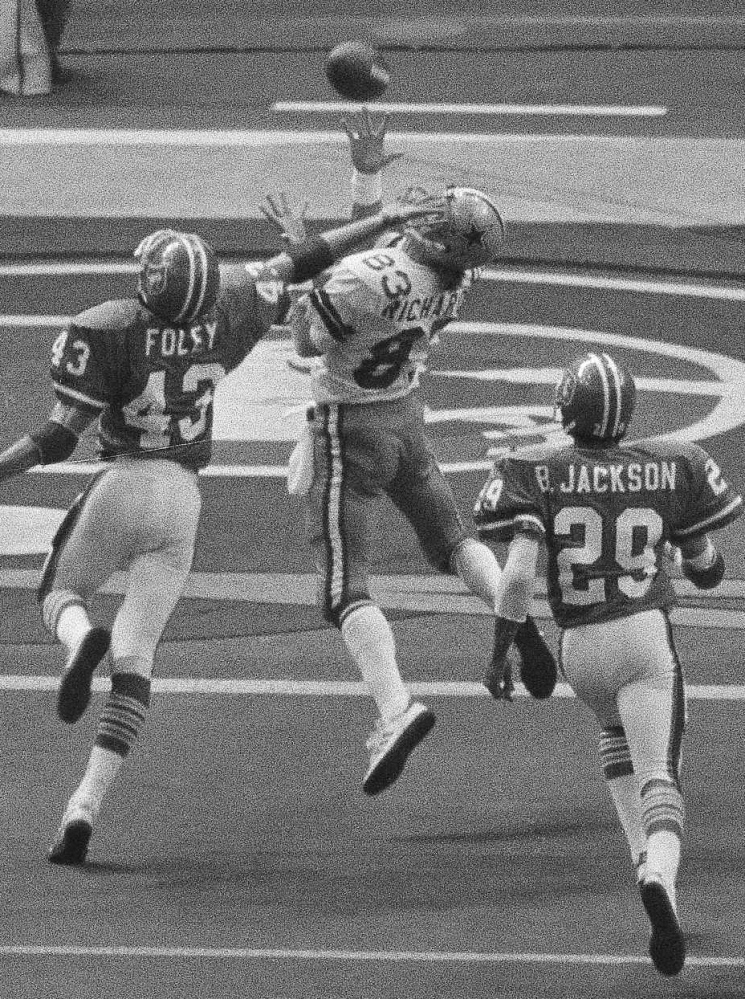 Despite the effort of Denver's Steve Foley, left, Dallas receiver Golden Richards, center, hauls in a touchdown pass from running back Robert Newhouse in 1978.