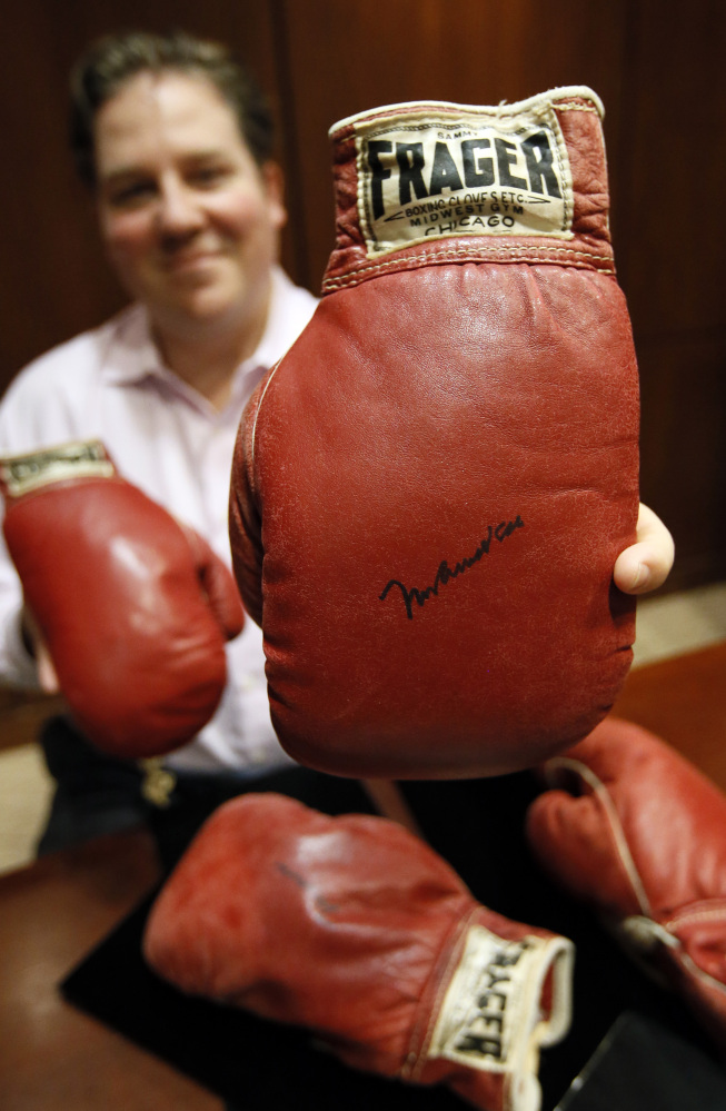 Chris Ivy, director of sports auctions at Heritage Auctions, holds the autographed gloves of Muhammad Ali with the gloves of Sonny Liston sitting on the table.