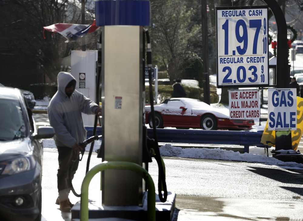 A motorist pumps gas at a station where the cash price for regular unleaded was under $2 a gallon on Jan. 9 in Leonia, N.J. For the first time since 2009, most Americans are paying less than $2 a gallon.
