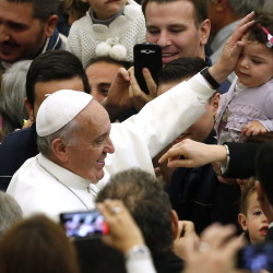 Pope Francis blesses a child as he arrives to lead a special audience for Vatican employees and their families at the Vatican last month.
