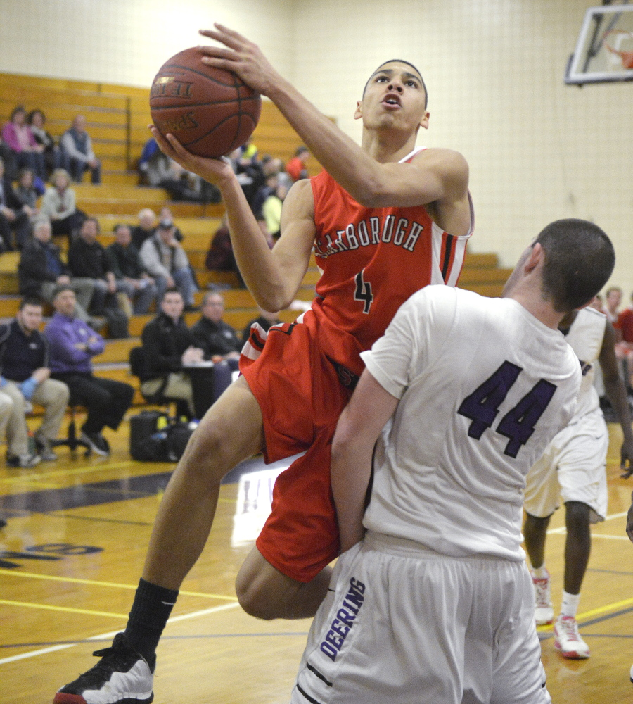 Milani Hicks, who scored 20 points for Scarborough, heads to the basket while guarded by Raffaele Salamone of Deering. The Rams improved their record to 10-4 and dropped Scarborough to 7-8.
