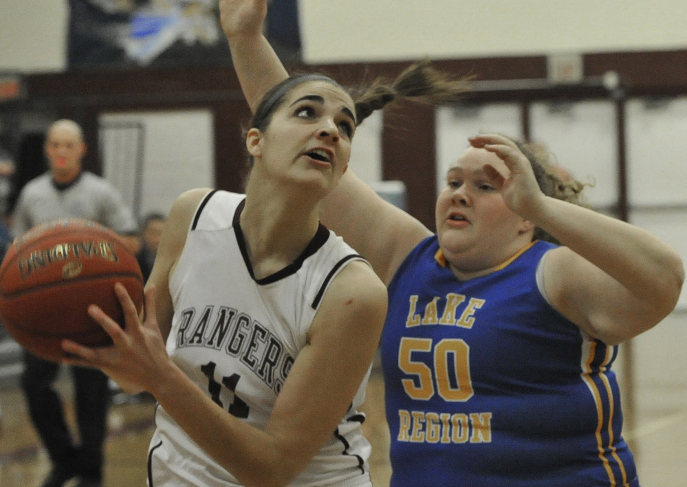 Ashley Storey, who finished with 19 points and 10 rebounds for Greely, looks for room while guarded by Megan VanLoan of Lake Region.