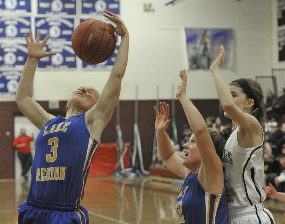 CeCe Hancock of Lake Region takes control of a rebound Friday night, pulling down the ball in front of her teammate, Sarah Hancock, during a 52-30 loss to Greely at Cumberland.
