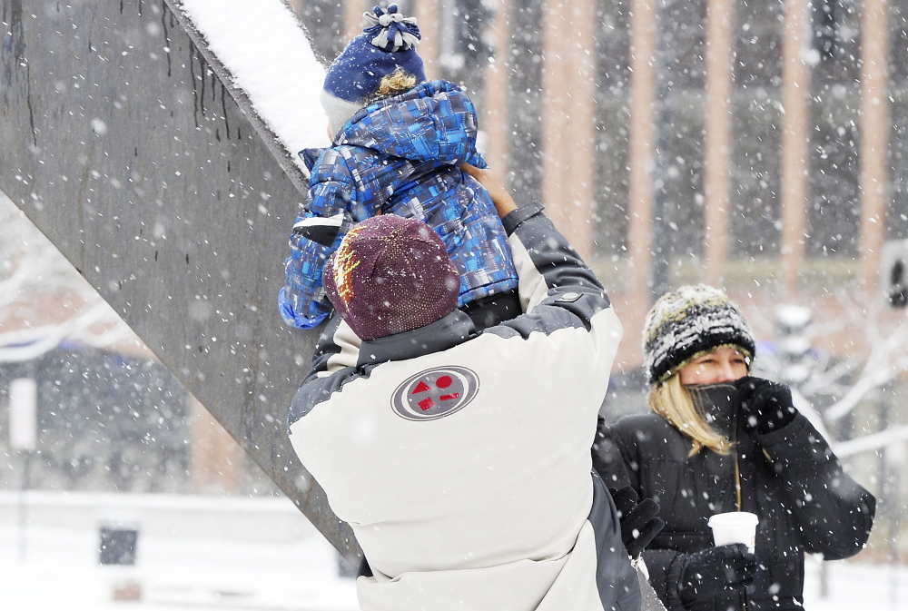 Snow falls as Lenny Medina helps his son, Odalis, slide on a metal sculpture in City Center Plaza on Saturday while Anna Medina, right, bundles up in the stormy weather.