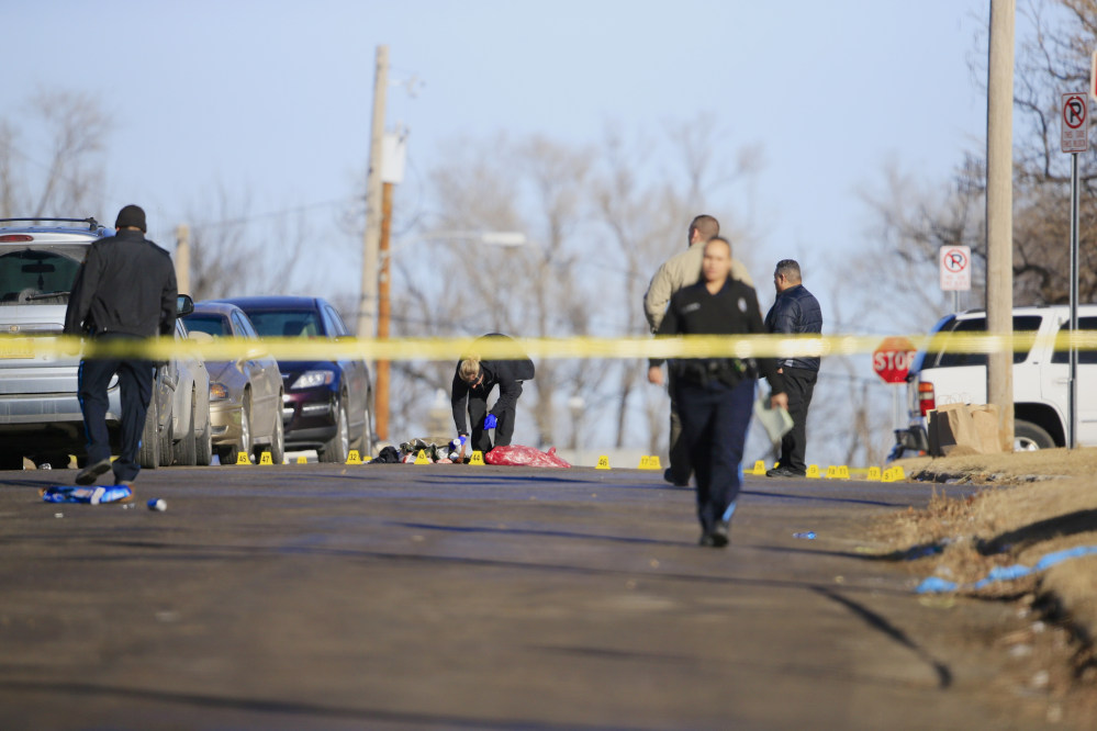 Crime lab investigator and police officers work the scene of a shooting in Omaha, Neb.