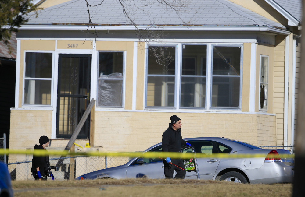 The Associated Press A crime lab investigators walk past a house where a shooting in Omaha, Neb., Saturday.