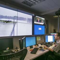 Shane McKenzie of Securitas monitors a screen at Central Maine Power's new security operations center in Augusta. A perimeter view of the Albion substation is transmitted by video cameras.
