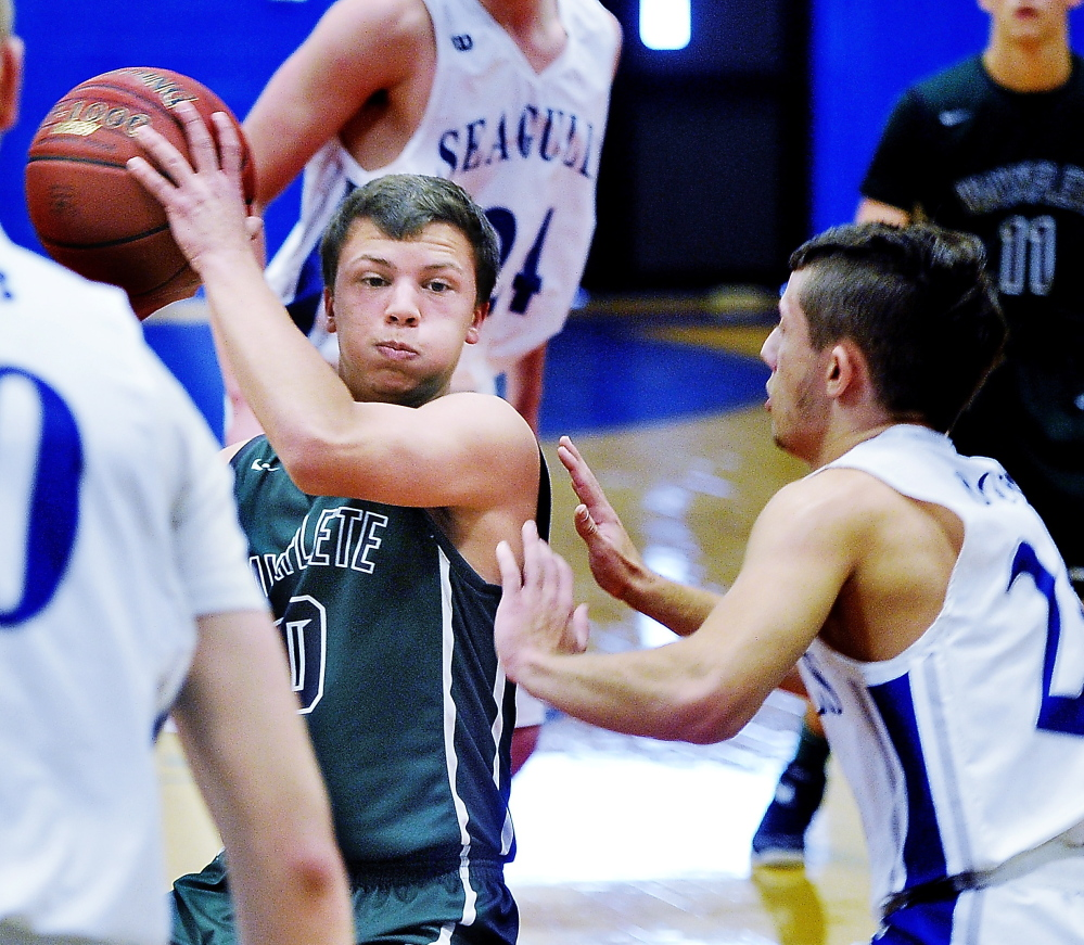 Will Burdick of Waynflete is closely guarded by Erik Hogan of Old Orchard Beach during their Western Maine Conference boys' basketball game Saturday. Waynflete completed a season sweep of the Seagulls with a 61-56 overtime victory.