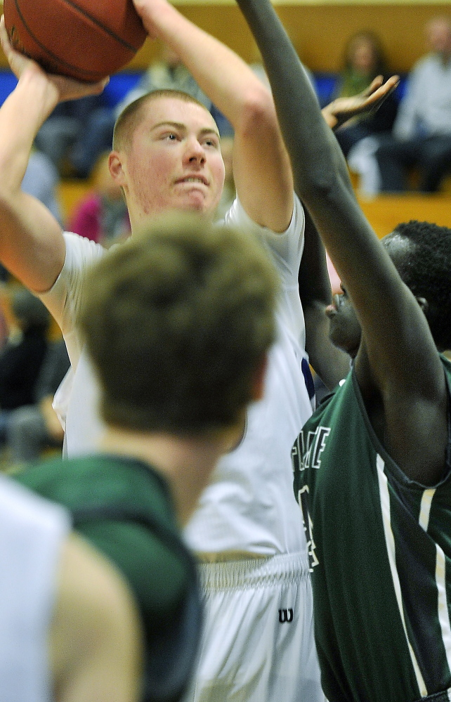 Zach Belanger of Old Orchard Beach looks for an opening to shoot against Waynflete's Yai Deng after pulling down an offensive rebound.