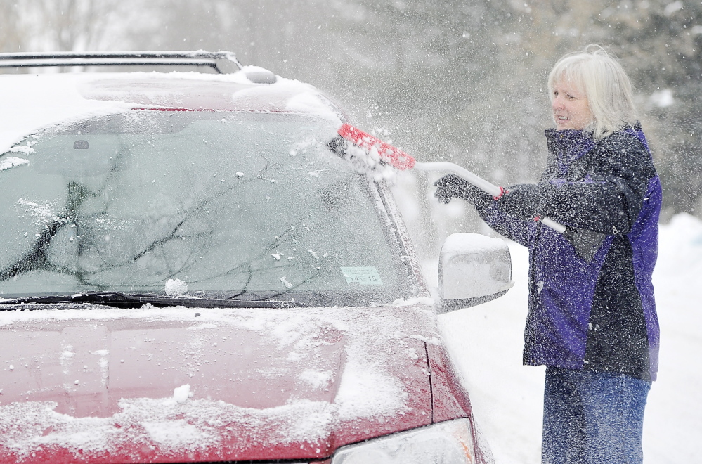 Cindy McGovern clears the snow from her van windows Saturday in the Riverside area of Portland.