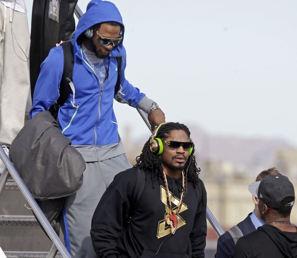 Seattle's Richard Sherman, back, and Marshawn Lynch arrive in Phoenix on Sunday to prepare for the Super Bowl. Sherman was critical of NFL Commissioner Roger Goodell.