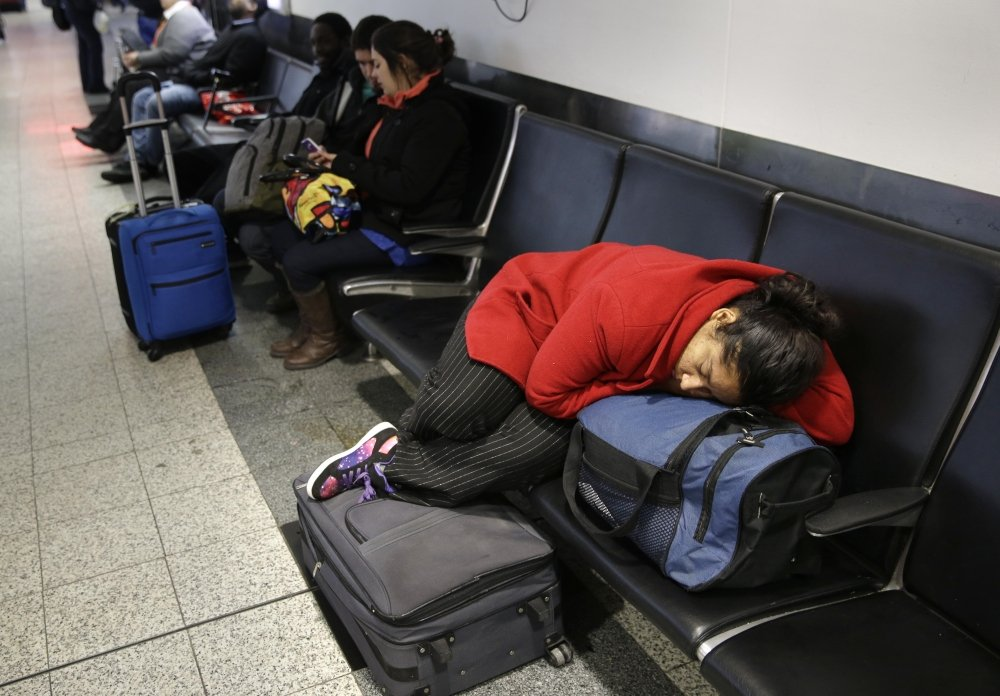A woman sleeps on top of her luggage at LaGuardia Airport in New York on Monday. Airlines canceled thousands of flights into and out of East Coast airports as a major snowstorm bears down on the region.