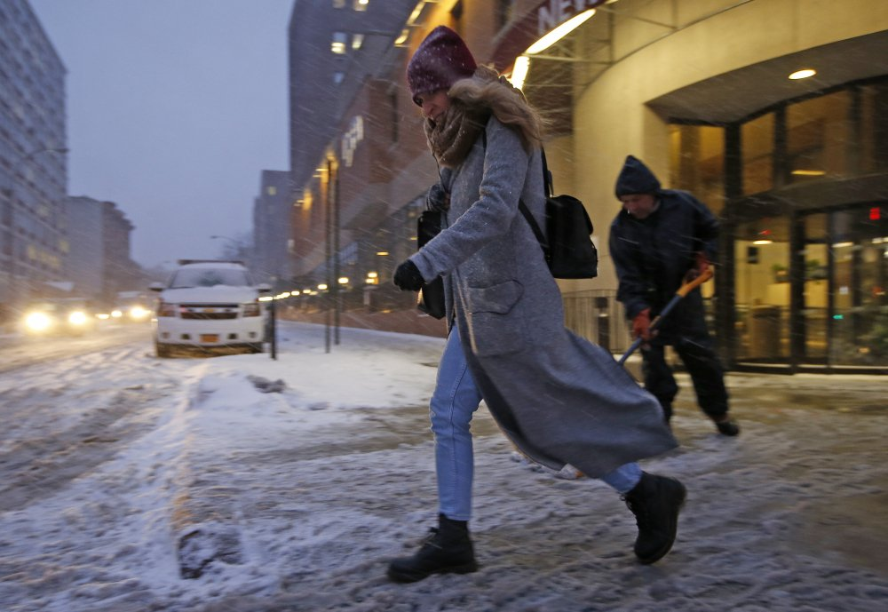 A woman makes her way across a slushy street Monday as a worker cleans the sidewalk in front of New York Methodist Hospital in Brooklyn. Cities from Boston to New York and Philadelphia began shutting down Monday against a monster storm that could unload as much as 3 feet of snow on a region of more than 35 million people.