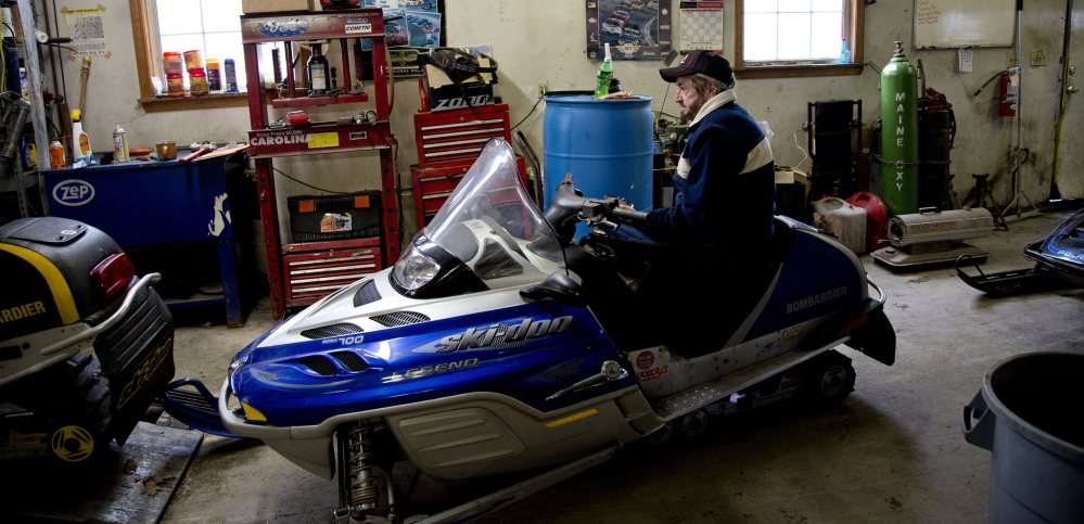 "Wayne Keniston, owner of Keniston's Auto & Snowmobile Supplies sits on a sled in his shop on the Gray Road in Falmouth on Monday. ""It's white gold for us.' he said of Tuesday's predicted snowfall.  Photos by Gabe Souza/Staff Photographer"