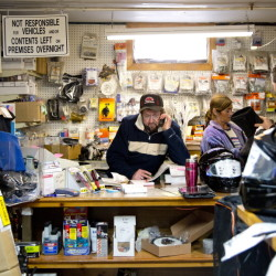 Wayne Keniston, owner of Keniston's Auto & Snowmobile Supplies in Falmouth, looks for a part for a customer in his shop on Monday. His shop was busy all day, with snowmobilers anticipating a storm that is predicted to dump as much as 2 feet of snow on much of Maine.