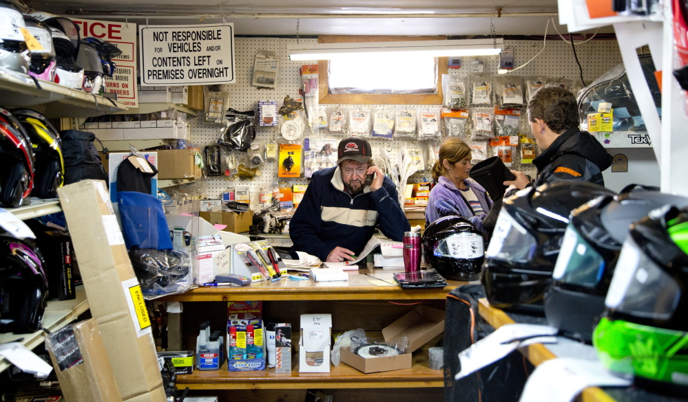 Wayne Keniston handles a call at his Falmouth store while shoppers anticipating good riding browse for snowmobile gear.