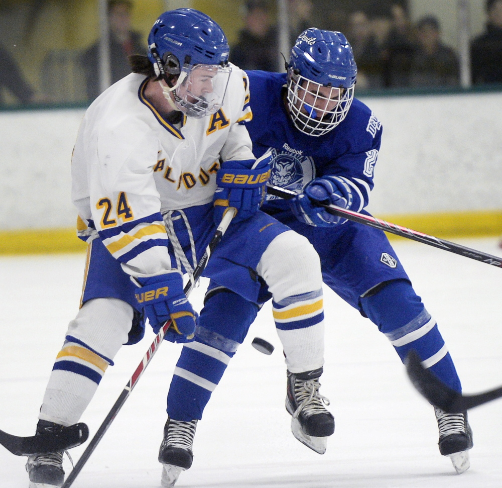Falmouth's Jake Grade, left, battles for the puck with Lewiston's Brendon Croteau during a 5-2 win by the Blue Devils at Falmouth on Monday. Lewiston improves to 8-3-1 with the win; Falmouth is 9-4.