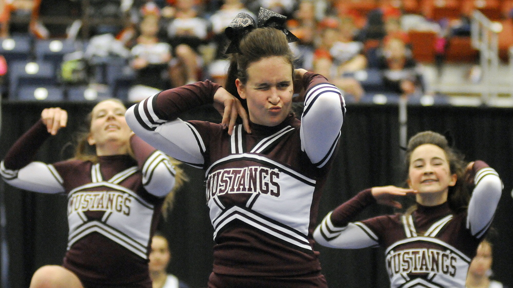 Members of the Monmouth Academy cheerleading team compete in the Western C championships Monday at the Augusta Civic Center. The Mustangs finished third to qualify for states. Andy Molloy /Kennebec Journal