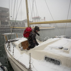 "As the wind howls and snow falls, Jack Marrie enters his 30-foot fiberglass ketch the Rime, where he lives year-round on the Portland waterfront. Marrie said he did nothing special to prepare for Tuesday's blizzard. ""I like a good storm,"" he said."