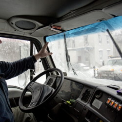 Bill Bushey, a snow plow driver with the city of Portland, waves to another driver as he works in Tuesday's blizzard.