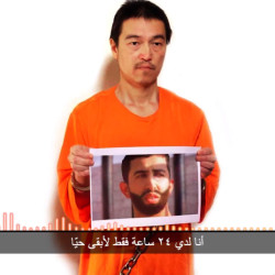 This image taken from a video posted on YouTube by jihadists Tuesday shows Japanese journalist Kenji Goto holding what appears to be a photo of Jordanian pilot 1st Lt. Mu'ath al-Kaseasbeh. The Associated Press