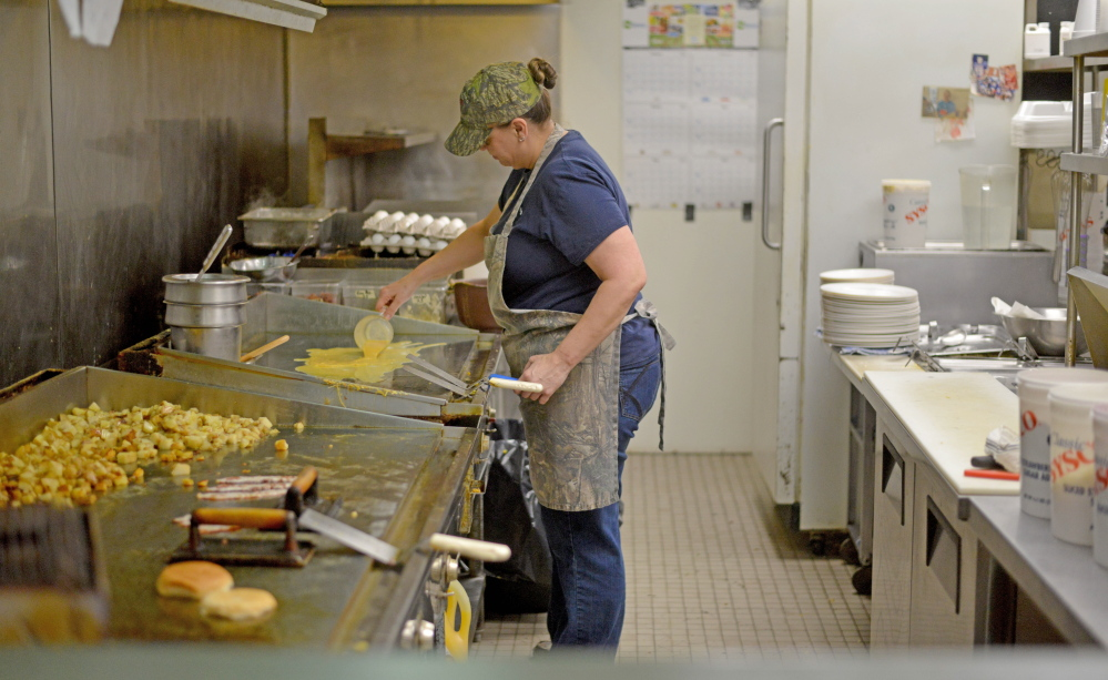 Gracie Furbush prepares food Tuesday in the kitchen at the Early Bird Restaurant in Oakland.