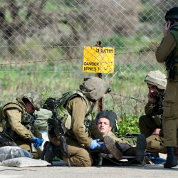 Israeli soldiers treat a wounded soldier near the Israel-Lebanon border, Wednesday.