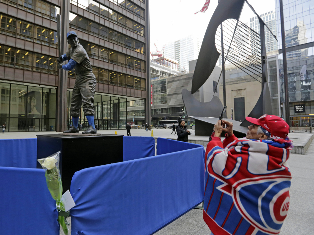 Baseball fan Geroge Valdez, 64, takes a photo of a statue of Chicago Cubs Hall of Famer Ernie Banks that was placed next to the Picasso statue in Daley Plaza, as baseball fans get their first chance to pay their respects, in Chicago.