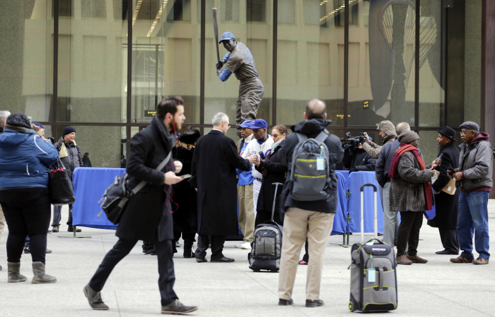 Baseball fans gather around the statue of Chicago Cubs Hall of Famer Ernie Banks that was placed in Daley Plaza, as fans get their first chance to pay their respects, Wednesday in Chicago.