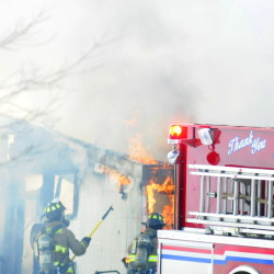 Firefighters pull back walls to expose fire as they extinguish a barn at 845 Northern Ave. in Farmingdale on Wednesday.