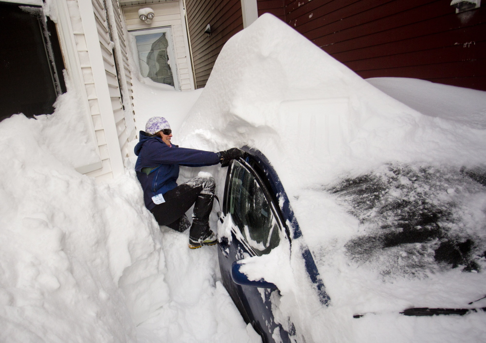 Bonnie Frye Hemphill yanks on her car door as she tries to wedge herself in while digging out of her driveway on North Street Wednesday after a blizzard dumped more than two feet of snow on Portland. Forecasters attach little meaning to predictions of more snow in the near future.