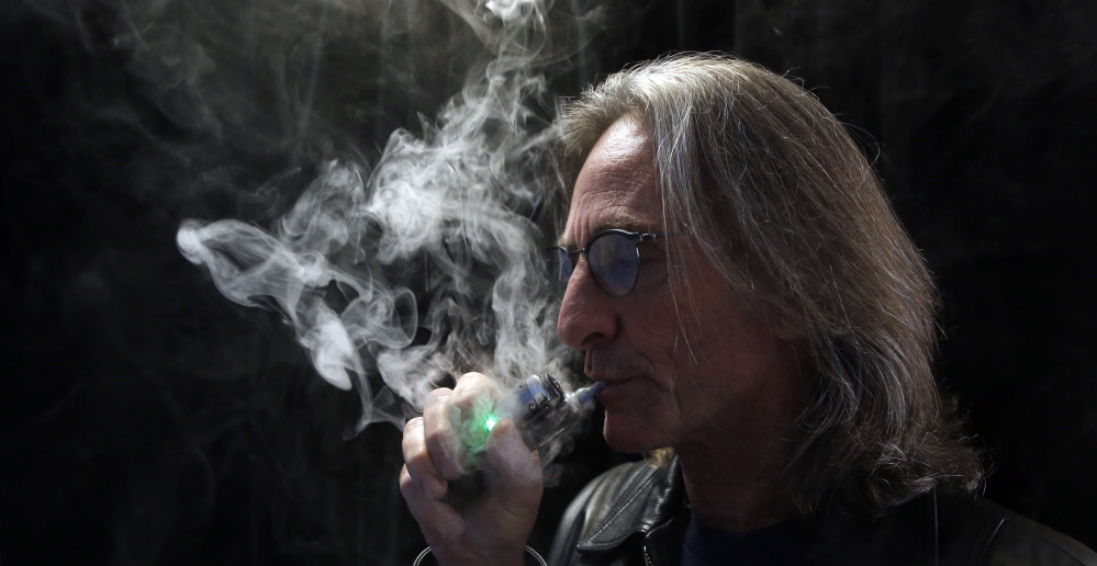 John Hartigan, proprietor of Vapeology LA, takes a puff of an electronic cigarette at his store in Los Angeles. The Associated Press