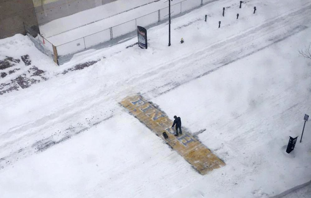 Chris Laudani, a bartender at the Back Bay Social Club, shovels snow from the Boston Marathon finish line on Boylston Street in Boston during Tuesday's winter storm that slammed eastern Massachusetts with as much as 2 feet of snow.