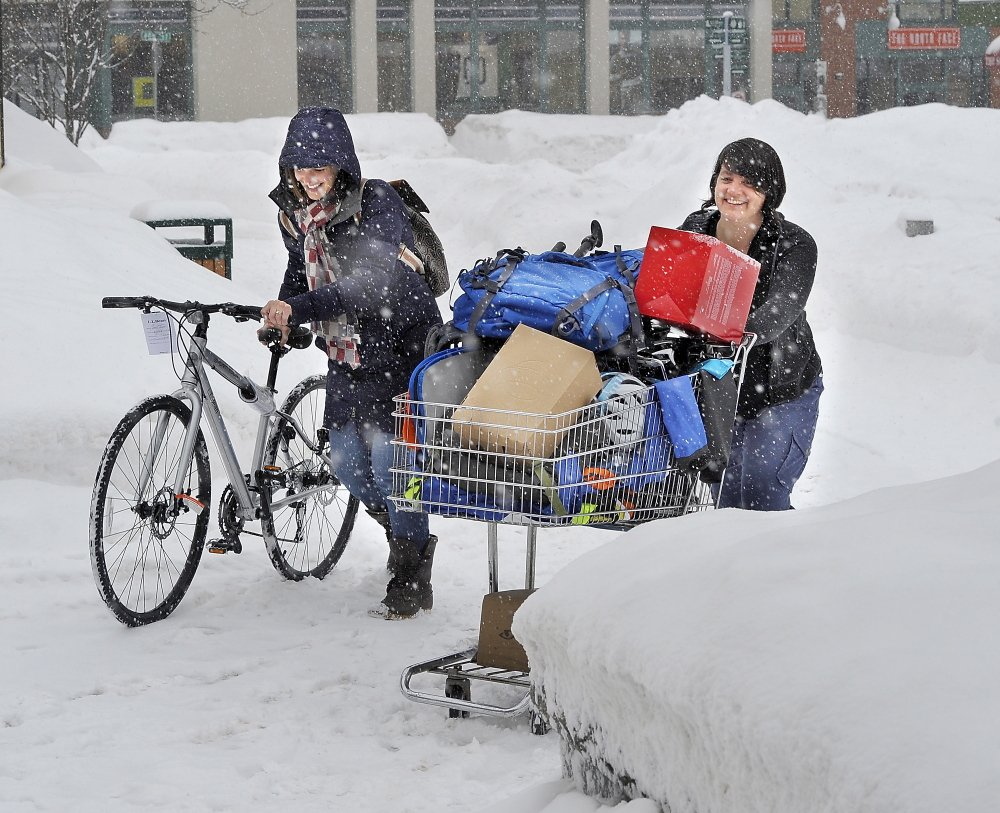 JAN. 30: Megan Hanson, left, and Justine Lasdin Springer, both of whom work as visual merchandisers for L.L. Bean, push a shopping basket of newly developed Bean products through the snow in Portland, three days after a massive blizzard swept across Maine.