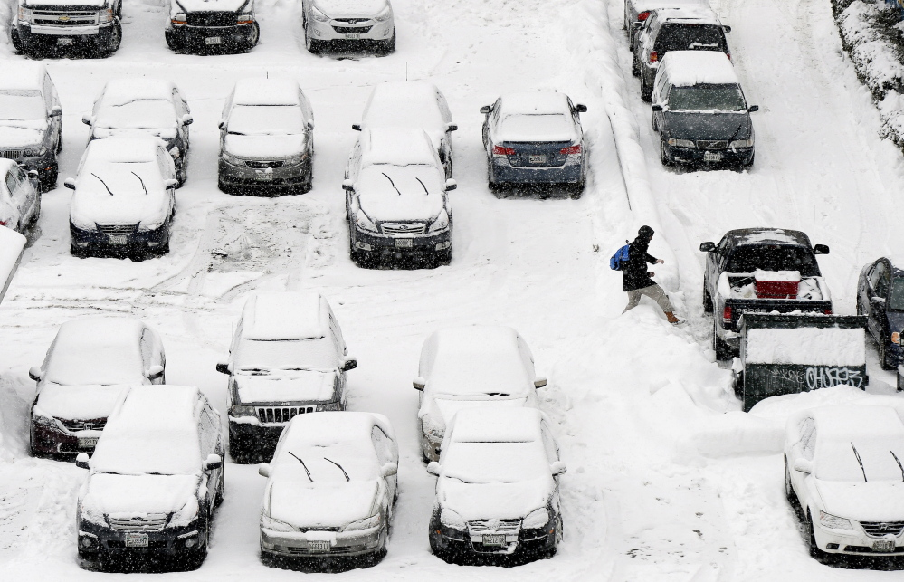 PORTLAND, ME - JANUARY 30: A man carefully steps over a snowbank in a snow covered parking lot on Free St. in Portland during Friday's snowfall January 30, 2015. (Photo by)