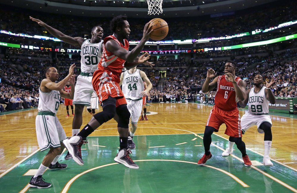 Houston Rockets guard Patrick Beverley looks to pass as he is pressured by Boston Celtics forward Brandon Bass (30) during the second quarter of Friday night's game in Boston. The Rockets won their fourth straight game.