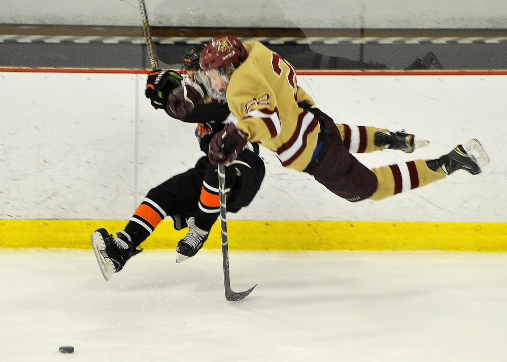 Biddeford's Joe Anders, left, and Thornton Academy's Chase Wescott are knocked off their skates after a collision. Anders was one of four goal scorers for Biddeford, which has lost only once in its last seven games.