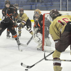 Tanner McFarren, right, of Thornton Academy looks for an opening to pass the puck to teammate Chandler Bilodeau, while Biddeford's Mike Reissfelder, left, and goalie Brandon Daigle defend Saturday at Biddeford Ice Arena. Biddeford won, 4-0.