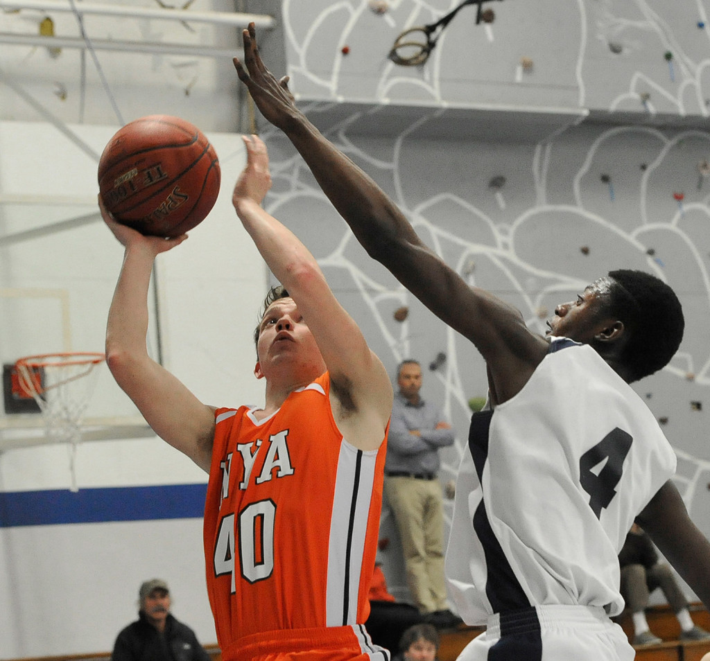 NYA's Patrick Jackson tries to shoot past Pine Tree Academy's JP Tshamala during a Jan. 21 matchup.