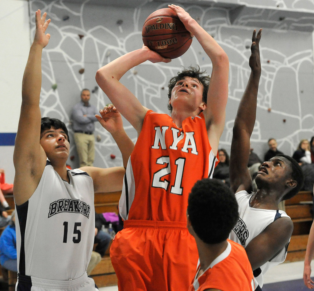 North Yarmouth Academy's Jake Malcom shoots the ball between Pine Tree Academy's Jon Krebs (15) and JP Tshamala during their Jan. 21 contest. NYA won, 42-33.